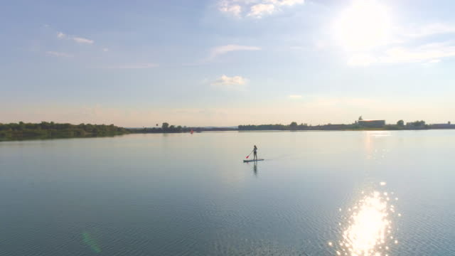 AERIAL Woman stand-up paddle boarding on a lake