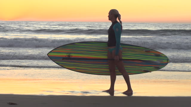 a woman stand-up paddleboard surfing at the beach. - slow motion - filmed at 240 fps - goodsportvideo stock videos and b-roll footage