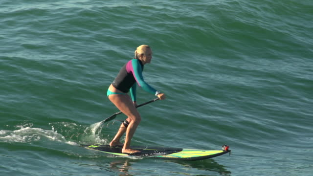 a woman stand-up paddleboard surfing at the beach. - slow motion - goodsportvideo stock videos and b-roll footage