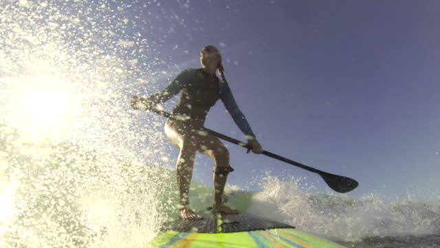 a woman stand-up paddleboard surfing at the beach. - goodsportvideo stock videos and b-roll footage
