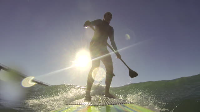 a woman stand-up paddleboard surfing at the beach. - einzelne frau über 30 stock-videos und b-roll-filmmaterial