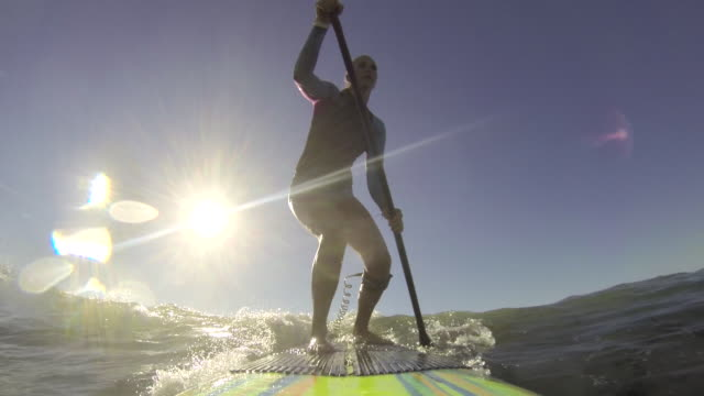stockvideo's en b-roll-footage met a woman stand-up paddleboard surfing at the beach. - alleen één mid volwassen vrouw