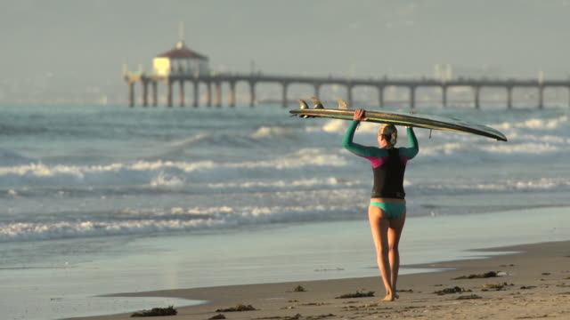 A woman stand-up paddleboard surfing at the beach.