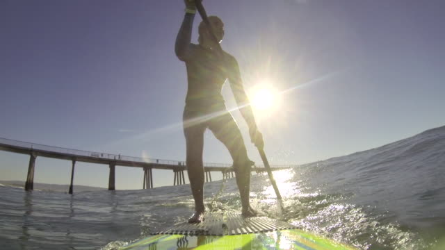 a woman stand-up paddleboard surfing at the beach. - 充足感点の映像素材/bロール