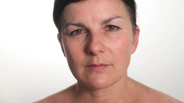 cu woman staring and blinking looking at camera. - ローストフト点の映像素材/bロール