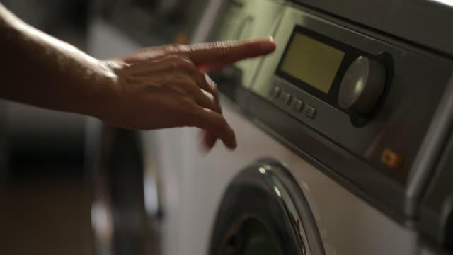 woman starting washing machine - washing machine stock videos and b-roll footage