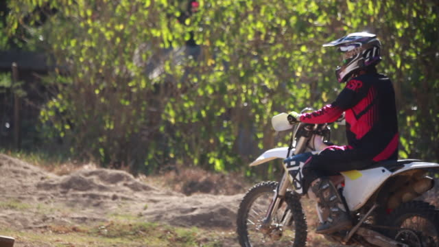 a woman starts a dirt bike and proceeds to ride it and then stops and looks around on a sunny summer day - kelly mason videos stock-videos und b-roll-filmmaterial