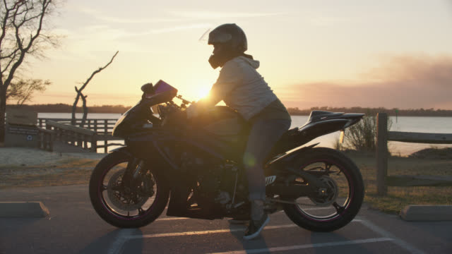 woman starts motorcycle and drives off as sun sets over river. - sturzhelm stock-videos und b-roll-filmmaterial