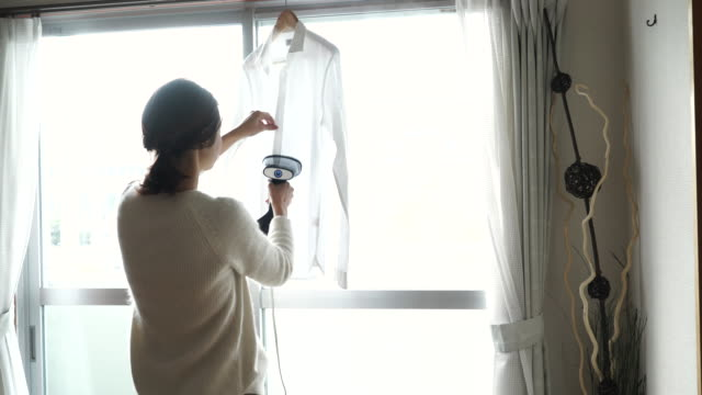 A woman steaming a shirt