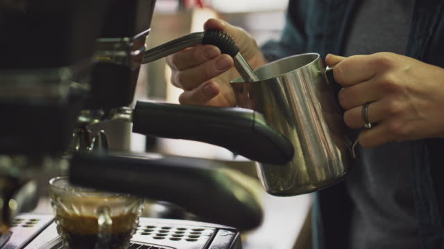 a woman steams milk in a metal carafe using an espresso machine - preparation stock videos & royalty-free footage