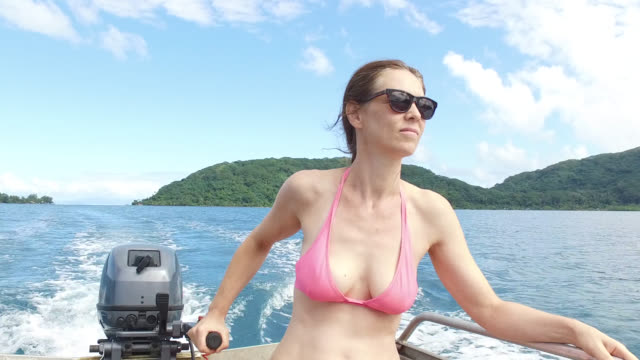 woman steering boat on water - huahine island stock videos and b-roll footage