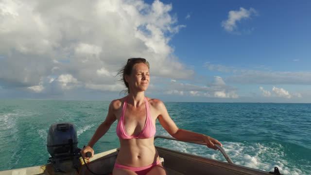 vídeos de stock e filmes b-roll de woman steering boat on water - ilha huahine
