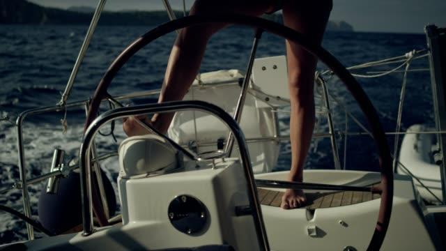 frau steuert die yacht mit bein - segelmannschaft stock-videos und b-roll-filmmaterial