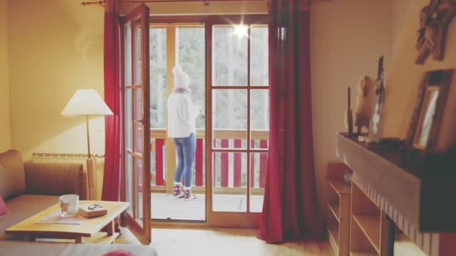 4K Woman stepping onto winter cabin balcony, real time