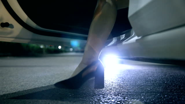 woman stepping out of car at night - abbigliamento formale video stock e b–roll