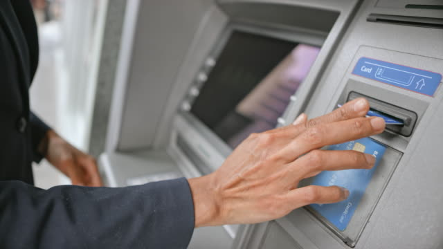 ld woman stepping to the atm to make a cash withdrawal - inserting stock videos & royalty-free footage
