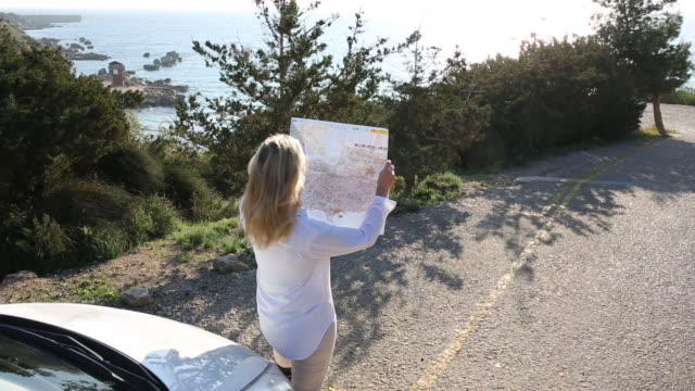 woman steps away from parked car, studies road map - road map stock videos & royalty-free footage