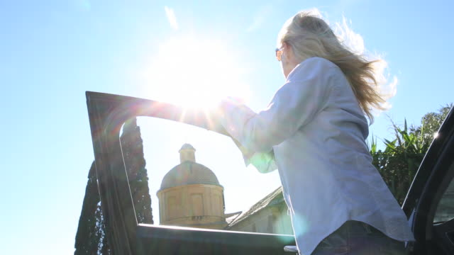 Woman steps out of car, looks to cathedral above