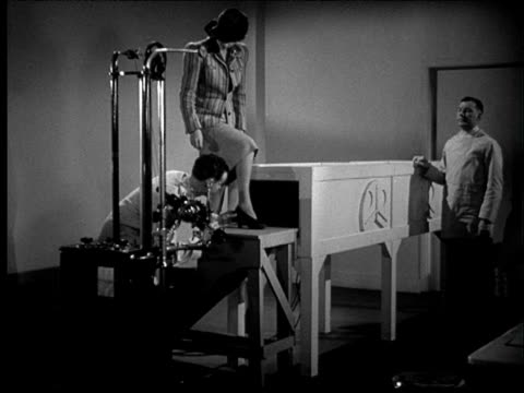 1941 b/w woman steps up on platform in front of x-ray machine; x-ray motion picture of woman's foot in high heel. - x ray equipment stock videos & royalty-free footage