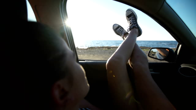 Woman sticking legs out of car window on road trip