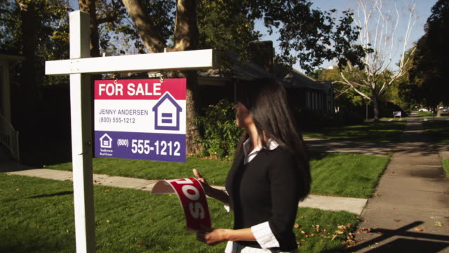 ms pan woman sticking 'sold' sign in front of suburban house / provo, utah, usa - selling stock videos and b-roll footage
