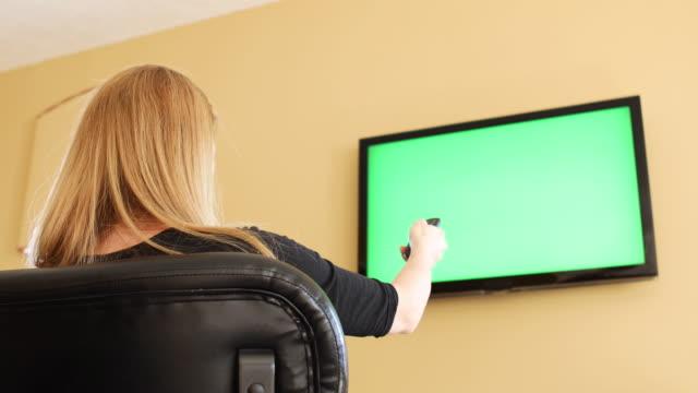 緑色の画面のテレビでチャンネルを変更する女性 stiiting - 居間点の映像素材/bロール