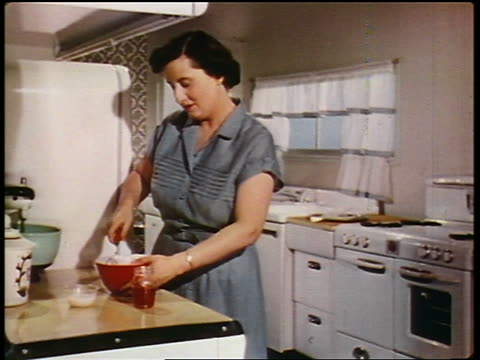 1950 woman stirring cream cheese topping in bowl on counter in kitchen - yorkville illinois stock videos & royalty-free footage