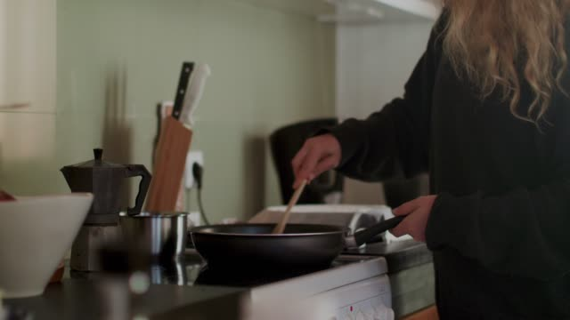 woman stirring food in frying pan with wooden spoon - viso naturale video stock e b–roll