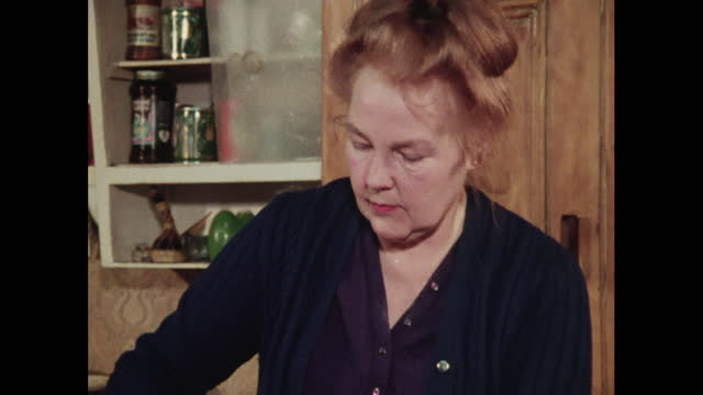 a woman stirs batter for a pudding, 1970s - raw food stock videos & royalty-free footage