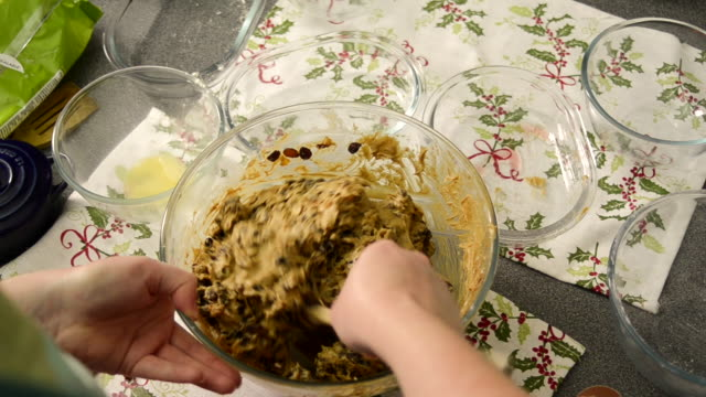 Woman Stirs Dried Fruit into a Christmas Fruit Cake Mix
