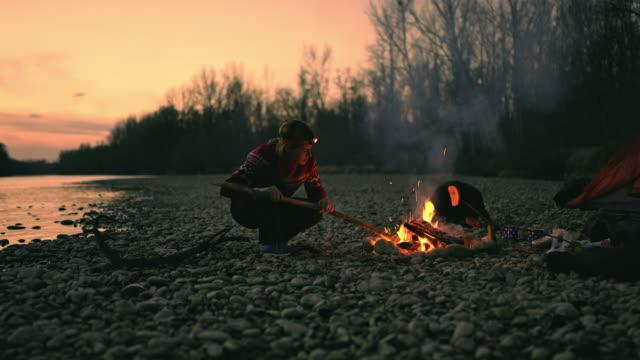 ms woman stoking campfire at autumn riverside,mur river,slovenia - fuoco acceso video stock e b–roll