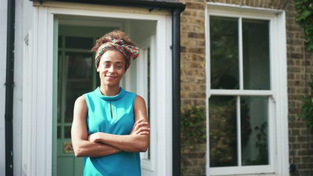 stockvideo's en b-roll-footage met woman stood outside her home, crossing arms, smiling - natuurlijk haar