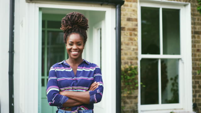 woman stood outside home and crossing arms, smiling - dreadlocks stock videos & royalty-free footage