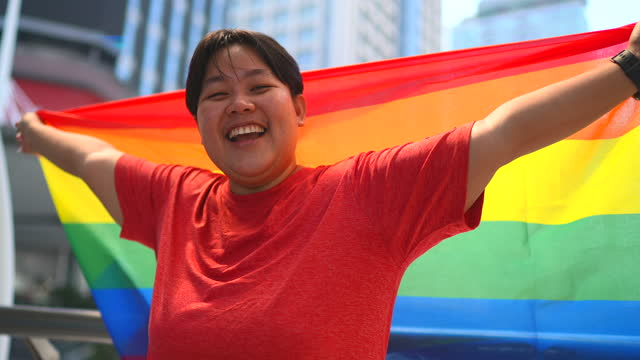 a woman stood smilingly, raising a rainbow flag. it is a symbol of lesbian, gay, bisexual, transgender, and queer (lgbtq) pride and lgbtq social movements. - gender stereotypes stock videos & royalty-free footage