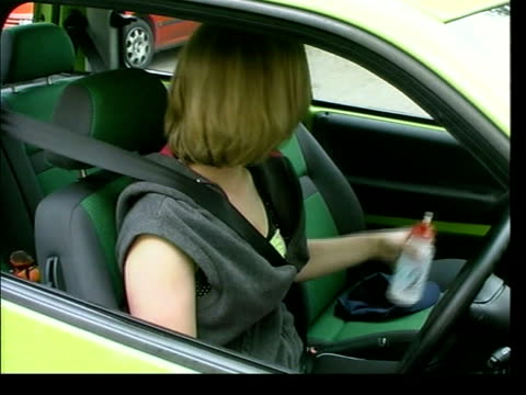 stockvideo's en b-roll-footage met woman stopped for drinking from water bottle itn wiltshire ext car driven by linda smart along pan smart sitting in car drinking from water bottle... - wiltshire