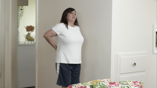 woman stops in home with back pain. - only mid adult women stock videos & royalty-free footage