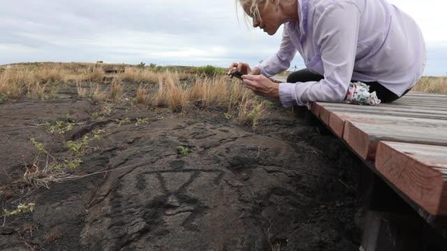 vídeos y material grabado en eventos de stock de mujer parada en el paseo marítimo, toma fotos de petroglifos - descubrimiento