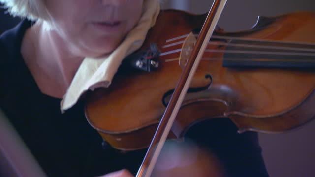 Woman stops playing violin