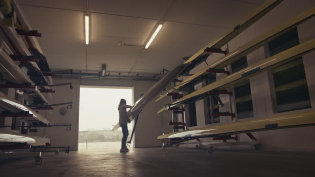 woman storing rowboat in boathouse - carrying stock videos & royalty-free footage