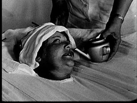 1953 CU woman strapped into hydrotherapy bath with towel on forehead as nurse pours drink into her mouth/  Norman, Oklahoma