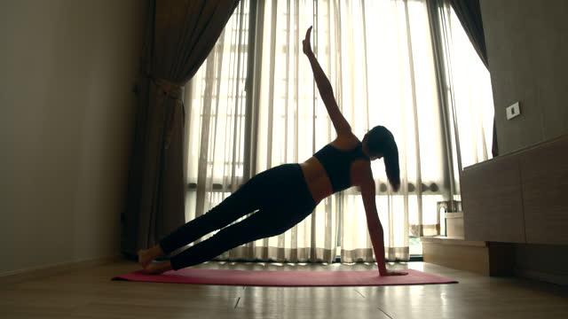 vídeos de stock, filmes e b-roll de mulher estressando fazendo exercícios de ioga na sala de estar da casa pela manhã - pose de arvore