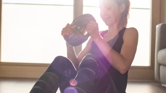 woman strengthening her core muscles on living room floor, doing russian twist exercises holding a weight plate - sit ups stock videos & royalty-free footage