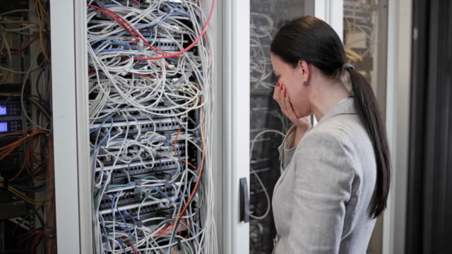 woman stressing about the cable mess in the server room and walking away - chaos stock videos & royalty-free footage