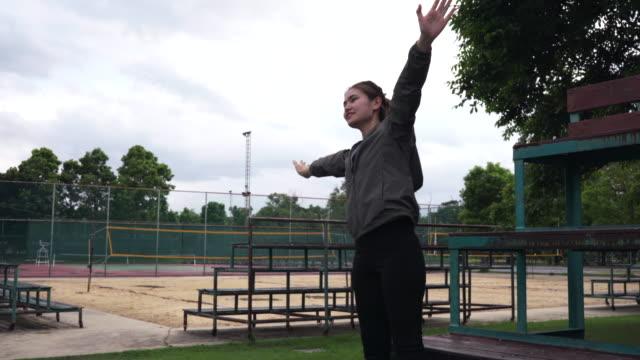 vidéos et rushes de femme elle étirer tout le monde, va pour exercer dans le parc extérieur. - joggeuse