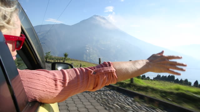 woman stretches arm out car window, on road below volcano - arms outstretched stock videos and b-roll footage