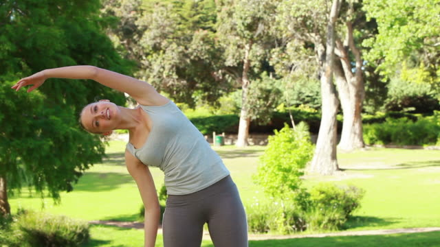 A woman stretches out her arms before going to train