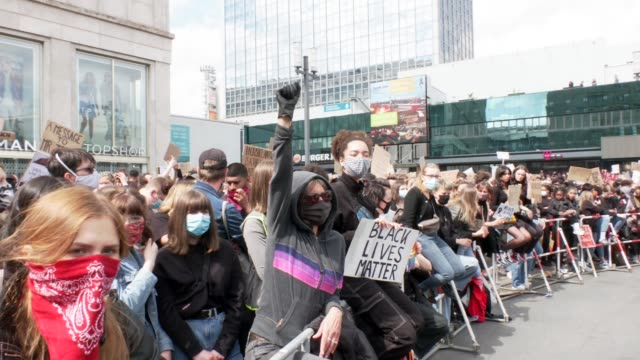 a woman stretches out her right hand to her fist clenched in a glove and protests with over 10000 people against racism and police brutality in... - glove fist stock videos & royalty-free footage