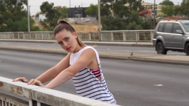 woman stretching along side a road - maglietta senza maniche video stock e b–roll