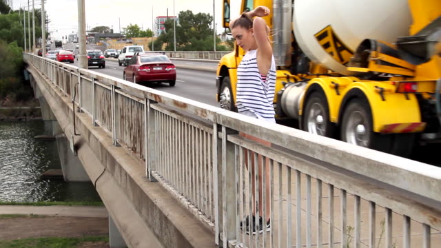 woman stretching alongside busy road - maglietta senza maniche video stock e b–roll