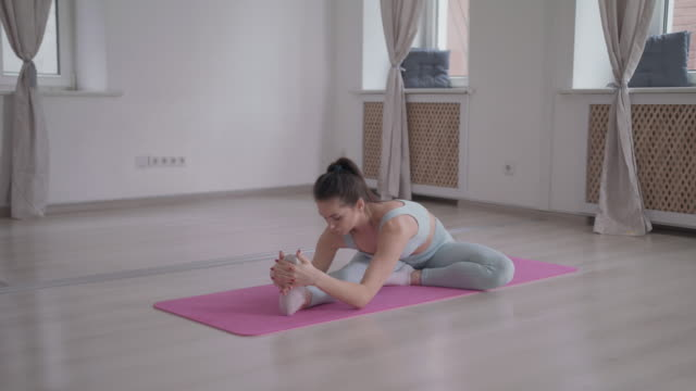 a woman stretching and calisthenics in a dance studio on a yoga mat. - dance studio stock videos & royalty-free footage